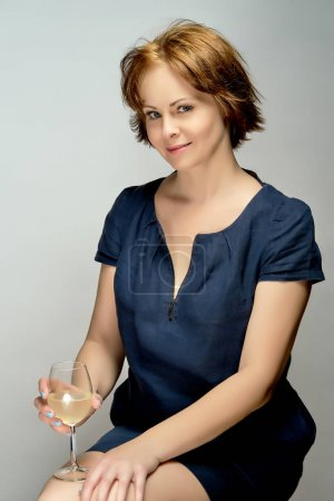 Photo pour Portrait de jeune belle femme aux cheveux roux avec verre de vin blanc sur fond gris en studio - image libre de droit
