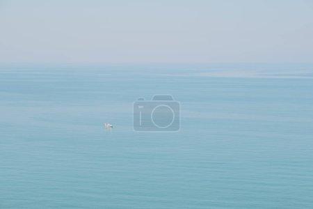 Photo pour Vue paisible et tranquille sur la mer, un petit bateau passant par là . - image libre de droit