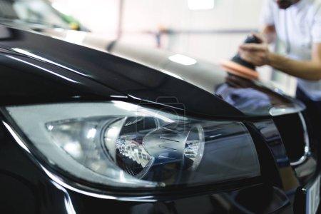 Photo pour Homme avec une polisseuse orbitale en atelier de réparation automobile. Mise au point sélective - image libre de droit