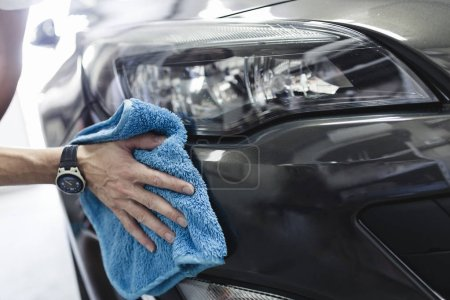 Photo for Man cleaning car with microfiber cloth, car detailing concept. Selective focus. - Royalty Free Image
