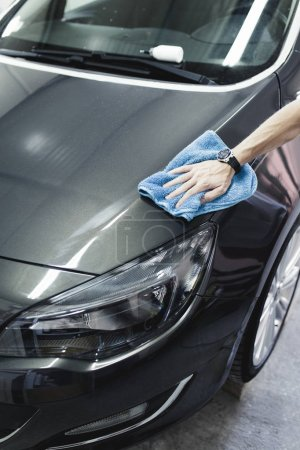 Man cleaning car with microfiber cloth, car detailing concept. Selective focus.