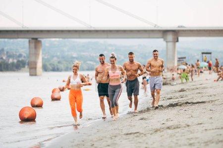 Photo pour Groupe d'entraînement de remise en forme de séduisantes jeunes. Ils s'amuser et courir sur la plage - image libre de droit