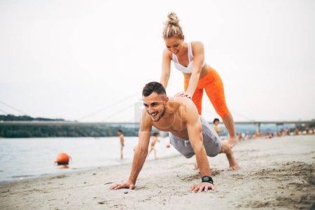 Photo pour Groupe jeunes gens attrayants s'amuser sur la plage et faire un peu d'entraînement de remise en forme . - image libre de droit