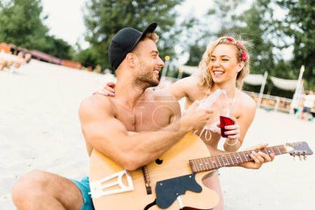 Couple of attractive young people enjoying at beach, drinking and playing guitar.