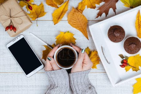Nicely manicured female hands holding cup of coffee on rustic wooden table with colorful autumn leaves, smartphone ans chocolate muffins. Autumn and winter theme. View from above.