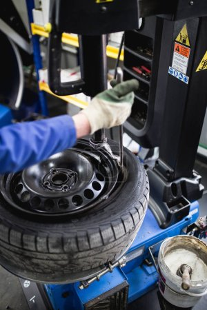 Photo for Mechanic repairing tire. Worker vulcanizing used tire. - Royalty Free Image