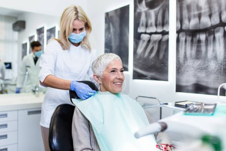 Photo for Portrait of smiling dentist and patient sitting at the table in dental clinic - Royalty Free Image