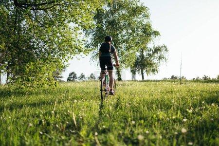 Cyclist man feet riding mountain bike on outdoor trail deep grass