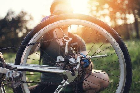 Photo for Bike repair. Young man repairing mountain bike in the field - Royalty Free Image