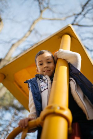 Photo for Cute and happy little boy enjoying and playing in autumn park. - Royalty Free Image