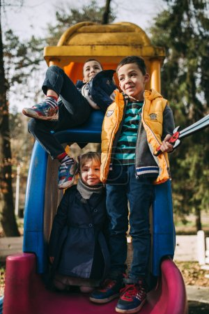 Photo for Brothers and sister kids playing in autumn park - Royalty Free Image
