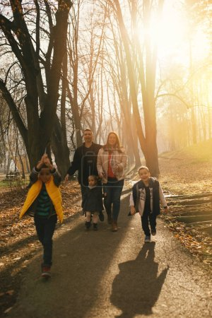 Photo for Happy young family enjoying in beautiful autumn day in park. They are smiling and walking on sunset. - Royalty Free Image
