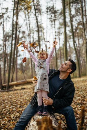 Photo for Happy young father with his doughter enjoying in autumn park. - Royalty Free Image