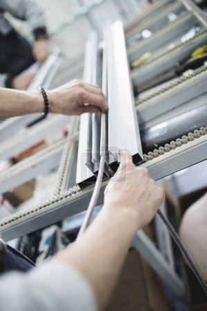 Photo pour Manual worker assembling PVC doors and windows. Manufacturing job. Selective focus. Factory for aluminum and PVC windows and doors production. - image libre de droit