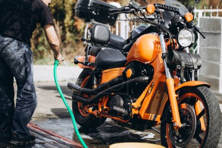 Photo pour Adulte et expérimenté motard nettoyage et lavage de sa moto - image libre de droit