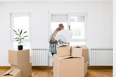 Photo for Happy middle aged couple with boxes moving into new home or apartment. Real estate theme. - Royalty Free Image