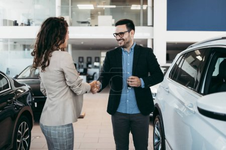 Photo for Happy middle age businessman buying new and luxury car. Beautiful female dealer gives him car keys. - Royalty Free Image
