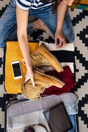 Photo pour Jeune femme touriste emballant ses affaires chaudes d'hiver et d'automne dans une grande valise. Concept de préparation au voyage. Vue du dessus ou vue du dessus. - image libre de droit