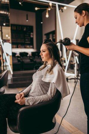Photo pour Belle femme brune aux cheveux longs au salon de beauté obtenant un coup de cheveux. Concept coiffure salon de coiffure. - image libre de droit
