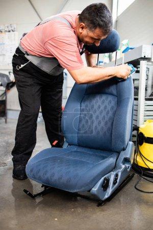 Photo pour Service de lavage de voiture travailleur nettoyage humide véhicule intérieur et sièges - image libre de droit