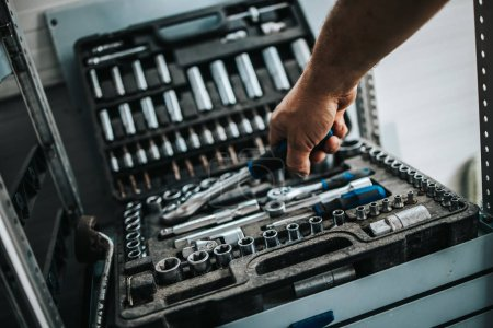 Photo for Close up shot of worker hand taking some professional tools from toolbox - Royalty Free Image