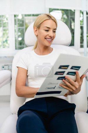 Photo pour Belle et heureuse femme blonde à la clinique médicale de beauté. Elle est assise et lit des informations cliniques sur les soins de beauté du visage et du corps. - image libre de droit