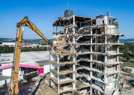 Photo pour Vue aérienne de la démolition de la maison et du chantier de construction Excavatrice avec machine hydraulique et conteneur jaune - image libre de droit