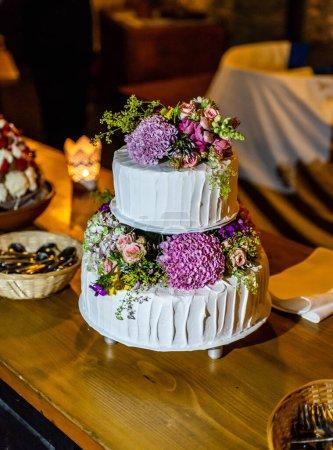 Photo pour Beau gâteau de mariage délicieux dans de nombreux niveaux avec des fleurs sauvages fraîches et des roses. - image libre de droit