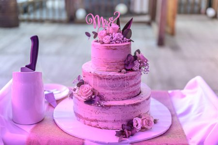 Photo for Beautiful wedding cake with cream With text MR MRS on top pink flowers roses. - Royalty Free Image
