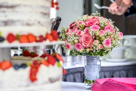Photo for Selctive Focus beautiful wedding flower bouquet behind delicious Wedding cake in many tiers with fresh wild berries and fruits - Royalty Free Image
