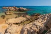 Rock on sandy sea resort beach in Costa Brava, Lloret de Mar