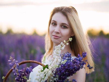 Photo pour Une belle jeune femme blonde en robe blanche pâle jouit de la nature. Champ de fleurs de lupin au coucher du soleil. Humeur rêveuse - image libre de droit
