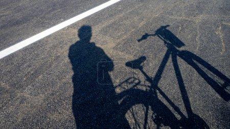 Photo for Bike and human shadow, bike and on asphalt road, - Royalty Free Image