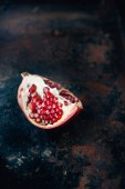 Quarter of pomegranate fruit on black rustic surface