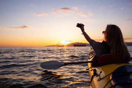 Woman on a kayak is taking selfies in the ocean during a vibrant sunset. Taken in Vancouver, British Columbia, Canada. Concept: adventure, holiday, lifestyle, sport, recreation, activity, vacation