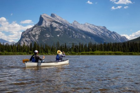 Photo for Vermilion Lakes, Banff, Alberta, Canada - June 19, 2018: Couple adventurous friends are canoeing in a lake surrounded by the Canadian Mountains. - Royalty Free Image
