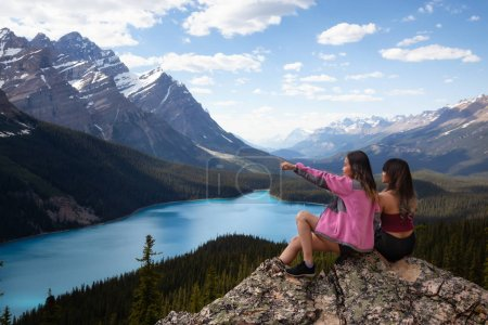 Adventurous female friends sitting on the edge of a cliff overlooking the beautiful Canadian Rockies and Peyto Lake. Taken in Banff National Park, Alberta, Canada.