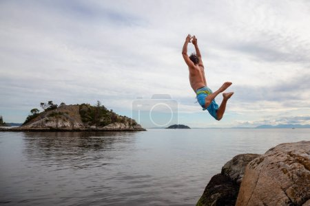 Adventurous man is cliff jumping from a rock into the ocean. Taken in Whytecliff Park, Horseshoe Bay, West Vancouver, BC, Canada.