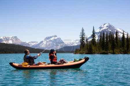Bow Lake, Banff National Park, Alberta, Canada - June 18, 2018: Couple of friends fishing on an inflatable kayak in a glacier lake.