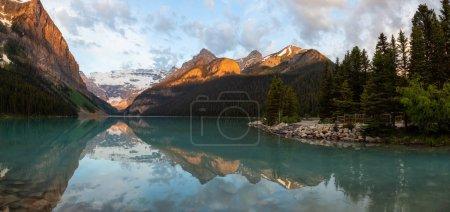 Photo pour Point de vue dans un lac glaciaire entouré de montagnes Rocheuses canadiennes lors d'un lever de soleil vibrant. Porté à Lake Louise, Banff, Alberta, Canada . - image libre de droit