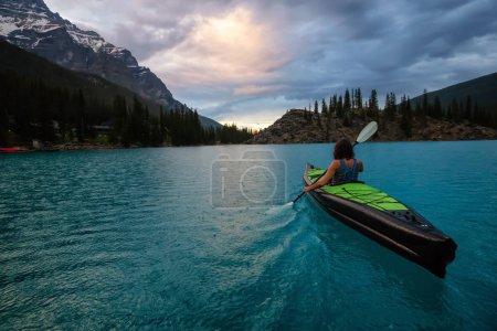 Adventurous woman kayaking in Moraine Lake during a striking cloudy sunset. Taken in Banff National Park, Alberta, Canada.