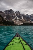 Kayaking in Glacier Water surounded by the beautiful Canadian Rocky Mountains. Taken in Moraine Lake, Banff National Park, Alberta, Canada.