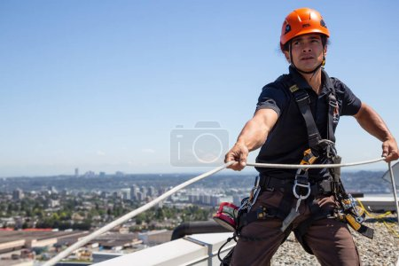 Burnaby, Vancouver, British Columbia, Canada - July 05, 2018: High rise rope access window cleaner is working during a hot sunny summer day.
