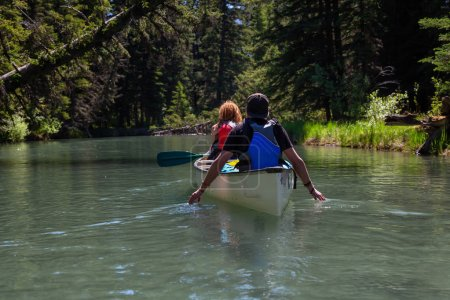 Couple adventurous friends are canoeing in a river surrounded by the Canadian nature. Taken in Vermilion Lakes, Banff, Alberta, Canada.