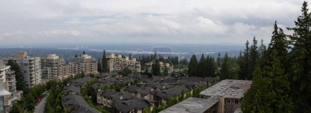 Aerial view of residential homes and buildings on top of Burnaby Mountain. Taken in Vancouver, British Columbia, Canada.