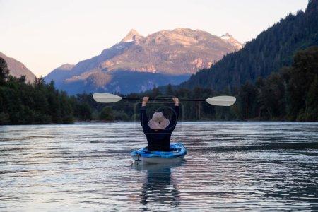 Photo pour Kayak dans une rivière entourée de montagnes canadiennes pendant un coucher de soleil de l'été animé. Prises à Squamish, Colombie-Britannique, Canada. - image libre de droit