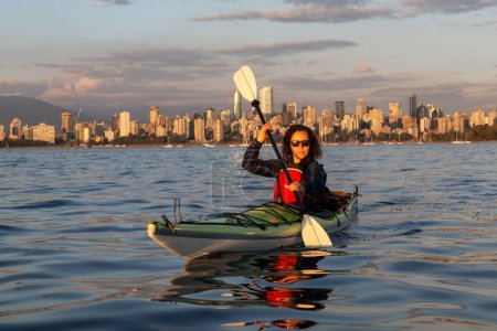 Girl Sea Kayaking in front of Downtown City during a vibrant sunny summer sunset. Taken in Vancouver, BC, Canada.