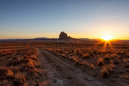 Photo for Striking landscape view of a dirt road in the dry desert with a mountain peak in the background during a vibrant sunset. Taken at Shiprock, New Mexico, United States. - Royalty Free Image