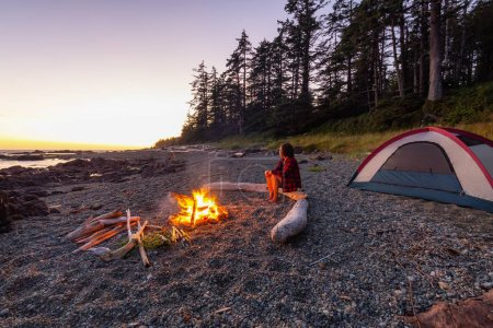 Photo for Camp fire on the beach during a vibrant summer sunset. Taken in Northern Vancouver Island Ocean Coast, BC, Canada. - Royalty Free Image