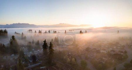 Photo pour Vue aérienne d'un quartier résidentiel recouvert d'une couche de brouillard lors d'un lever de soleil vibrant. Prise dans le Grand Vancouver, BC, Canada . - image libre de droit